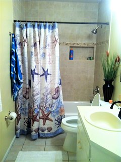 Guest bath by front two bedrooms, has tub/shower combo, single sink, tropical colors, updated.