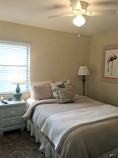 Guest bedroom #1 with queen size bed, flat screen tv, updated light colors tropical decor,
