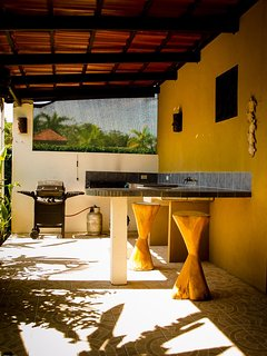 Outdoor kitchen with gad BBQ, large sink and bar stools