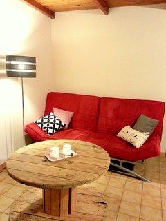 Coin salon face au poele à bois avec un canapé lit