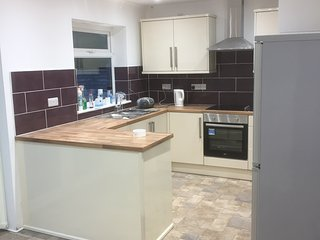 New kitchen with cooker dishwasher washing machine kettle toaster Microwave large fridge freezer.