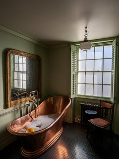 The bath is set between shuttered, frosted windows and a huge vintage mirror