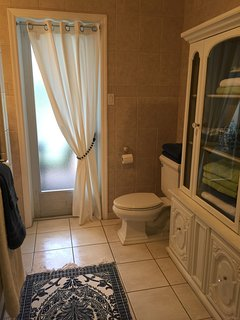 Guest bathroom with separate door leading directly to pool and lanai.