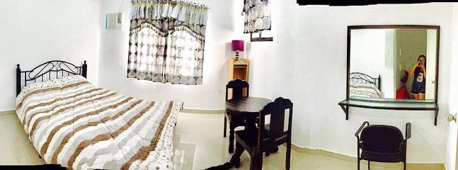 A double  bedroom with double bed airconditioned and mountain view , coffe table and dresser