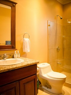 The third bathroom is located beside the guest room with 2 single beds