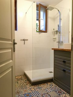 A completely renovated Salle de Bain features a rain shower head and fun tiles.