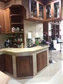 Indoor kitchen is equipped with coffee maker, coffee grinder, variety of coffees and teas, spices.