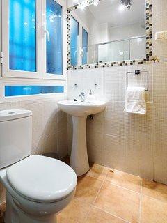 Cuarto de baño con espejo de grandes dimensiones.