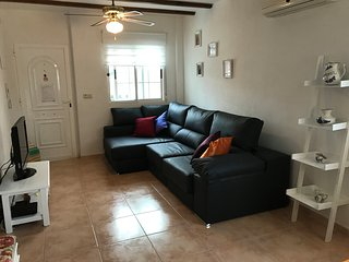 Bright living room with front and side window for extra breeze