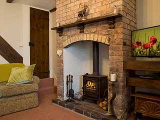 As you walk into the living room you notice the beamed ceilings and welcoming wood burner.