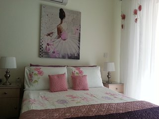 main bedroom with air con and ceiling fan, patio doors with fly screen. dressing table and stool
