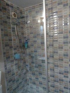 Cuarto de baño con plato de ducha y mampara.