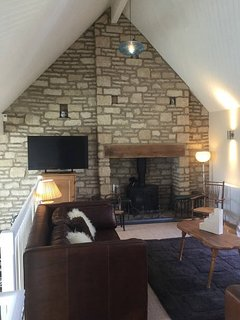 The sitting room has a lovely feeling of volume, with its pitched roof and feature stone wall.