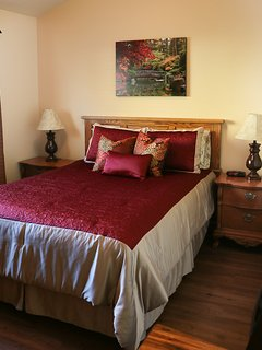 Bedroom with queen size bed, dresser and bedside tables with alarm clock.