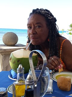 Guest sipping coconut water as we dine at the Round Hill Resort, near the beach.