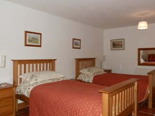 Twin bed room with  tiled floor adjoining is a en-suit  disabled shower room with easy access