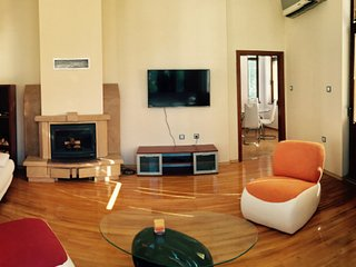Spacious living room with fireplace, TV, Aircondition and view to the dining table in the kitchen