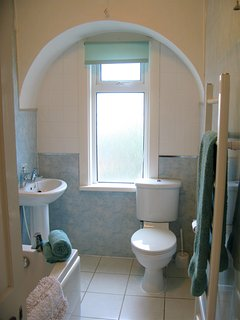 Main family bathroom, with full-size bath with shower and heated towel rail.