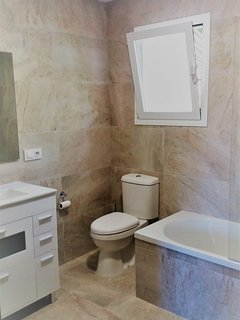 Completely modernised, fully tiled luxury family bathroom with bath, shower, heater and storage.
