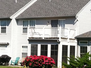 View of the rear of the home with sunroom and upstairs balcony