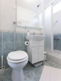 Bathroom with shower, washing machine, sink and toilet.