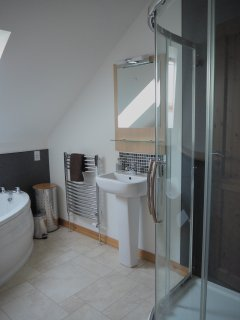 Bathroom with toilet, sink, corner bath and large separate shower. With sea views.
