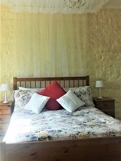 Double bed with canopy with views over the garden and the valley beyond.