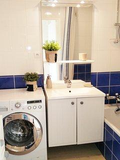 Salle de bain avec baignoire, douche et machine a laver