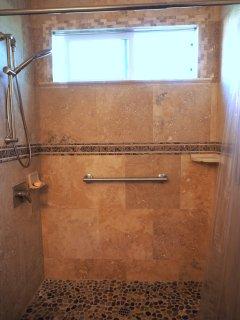 Luxury travertine shower. Adjustable three function shower head with rain shower option