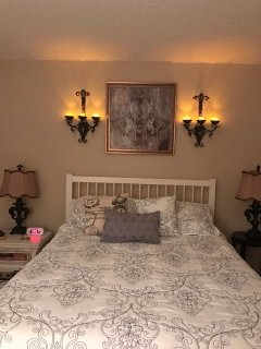 Oooo la la ...chandelier sconces with battery candles above the queen size guest bed.