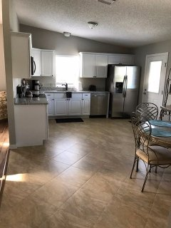 Large kitchen with stainless steel appliances. Fridge has an in the door ice & water dispenser.