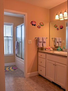 This bathroom features a shower/tub and double vanity.