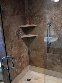 Large marble shower has a bench and a bench.