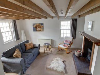 Double aspect lounge with wood-burning stove, TV & spiral staircase leading to the bedroom