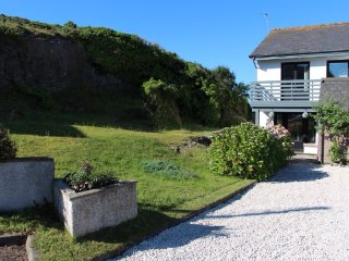 Large grassed area with rock-face on one side of the house