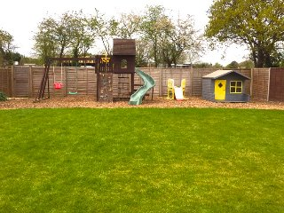 Kids play area with a climbing frame, slide, swings, and playhouse with kitchen.