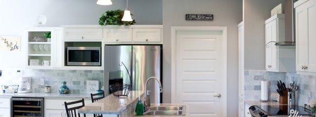 Bonita y amplia cocina con electrodomésticos de acero inoxidable y refrigerador de vino