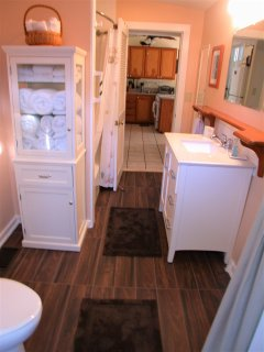 Bathroom offers tub and shower and is accessible from kitchen and bathroom as well as back deck.