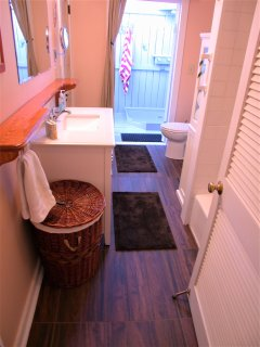 Bathroom opens to back deck with outdoor shower and sink.