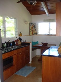 Kitchen with dinette table, fridge, microwave, and two burner stove-top
