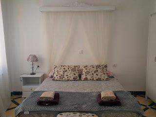 Una habitación con cama doble de matrimonio, con un armario, una cómoda y una mesilla.