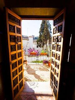 Puerta de cuarterones que da entrada a nuestra y jardín al fondo