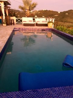 Cobalt blue glass tile surrounds the stunning swimming pool with one of the best views on island