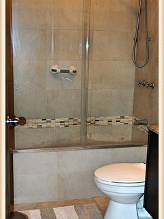 Upstairs, there is a full bathroom with a shower and tub.