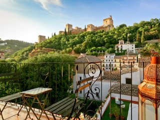 Balcony overlooking the Alhambra with a small table and 2 chairs.