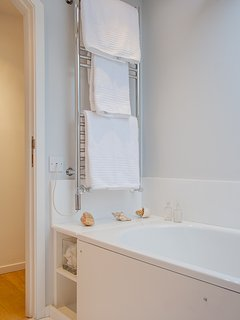 heated towel rail in family bathroom with fluffy white cotton towels