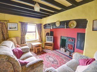 A characterful sitting room with beamed ceiling and open fire in the beamed fireplace