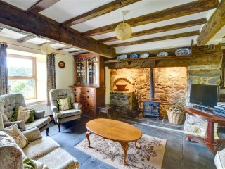 This traditional sitting room has a woodburning stove in the large beamed inglenook fireplace