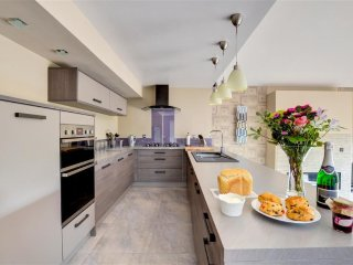 The modern fitted ktichen is smooth and sleek, and guests are welcomed by flowers, home-made bread, jam and cakes
