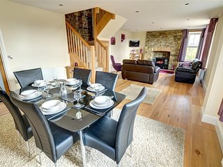 The modern looking living room has a dining area with table and six chairs